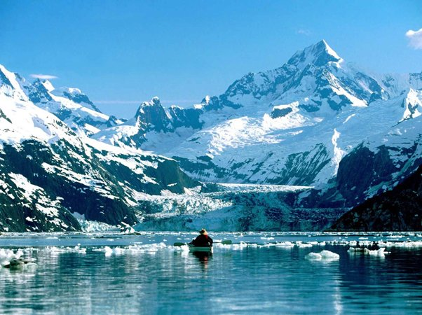 Picture of a man in a boat in icy waters below a mountain